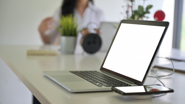 Laptop blank screen and smartphone on wireless charger