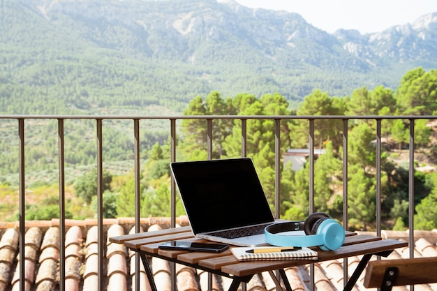 Laptop, blue headsets, a notebook, and a cellphone on the table on a balcony with a beautiful view
