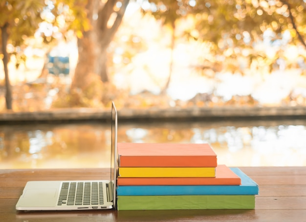 Laptop and books on the table for education.