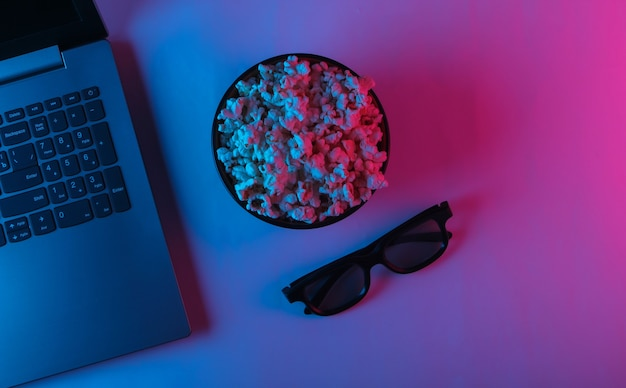 Laptop and bowl of popcorn, 3d glasses with blue pink neon light.