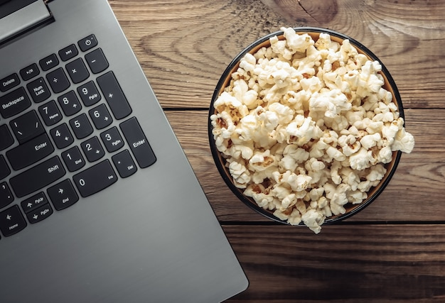 Laptop, bowl of popcorn on wooden table