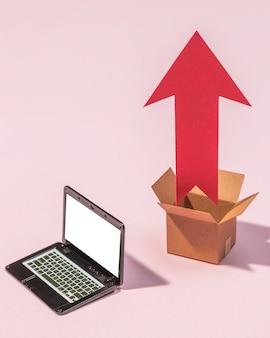 Disposizione laptop, scatola e freccia