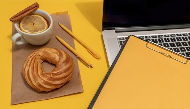 Laptop, cake, cup of tea and resume sheet on the fortuna gold yellow colour