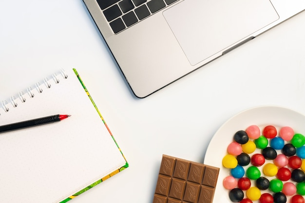 Laptop, candy and workbook with bar of chocolate and coffee at workplace.