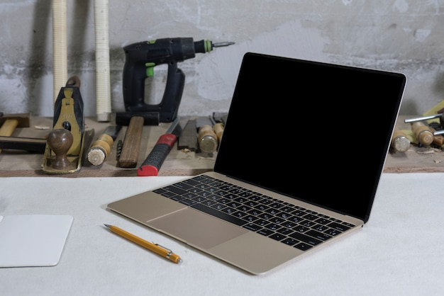 Laptop in a carpentry workshop on a workbench, tools and a drill in the background