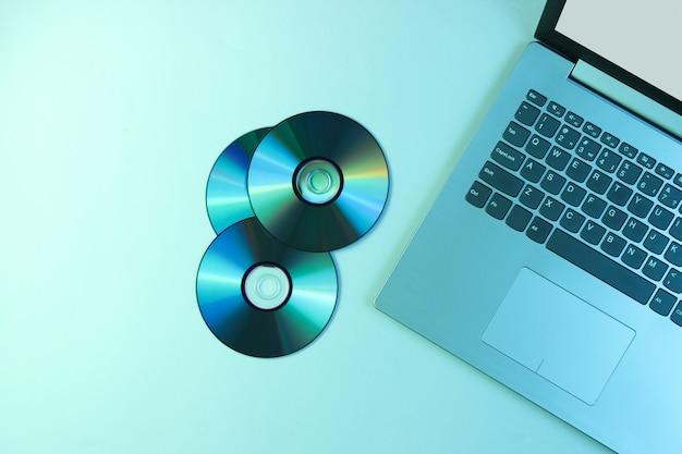 Laptop, cds. holographic light.