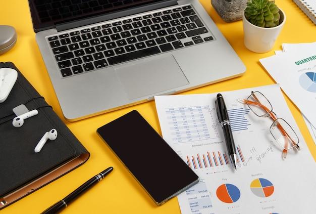 ノートパソコン、携帯電話、黄色い机の上の書類をクローズアップ。ビジネスコンセプト