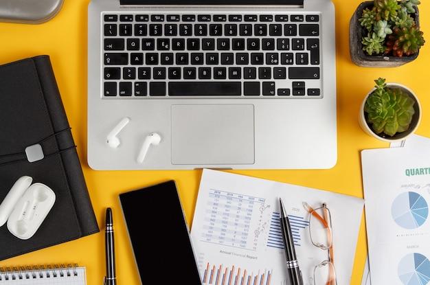 노란색 책상 위에 노트북, 휴대 전화 및 문서보기