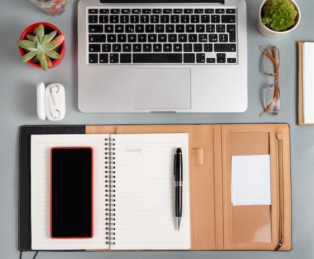 노트북, 휴대 전화 및 회색 책상 상단보기에 열린 의제. 비즈니스 개념