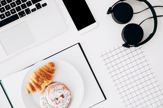 Laptop; cellphone; headphone; square grid paper; baked croissant and buns on diary over white background