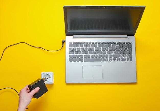 노트북 충전기 및 노란색 테이블에 전기 콘센트. 전기 중독의 개념. 평면도