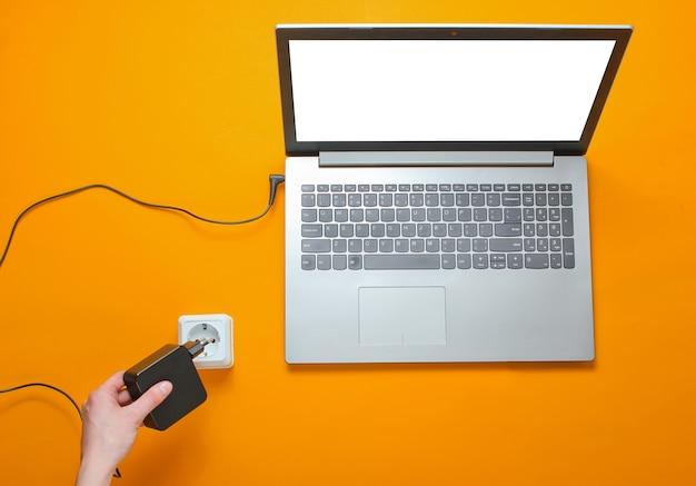 노트북 충전기와 오렌지 배경에 전기 콘센트입니다. 전기 중독의 개념. 평면도