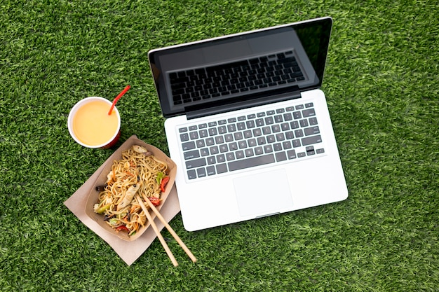 Laptop and chinese food on grass background