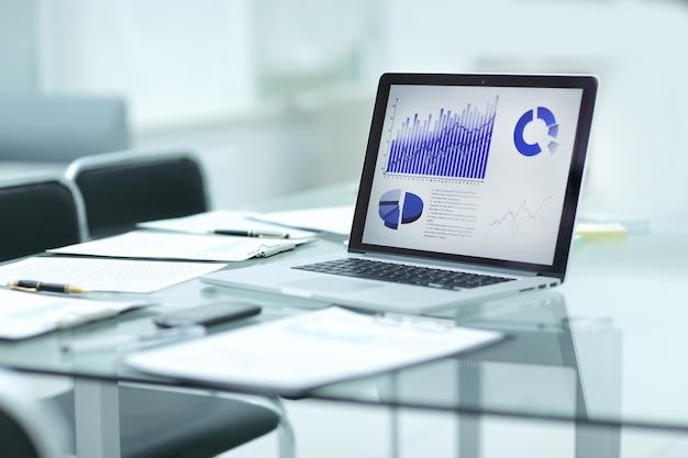 デスク上のラップトップ、クリップボード、財務データ