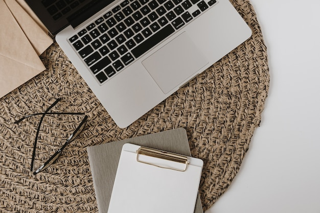 Ноутбук, буфер обмена, конверт на фоне ротанга. плоская планировка, эстетичный минималистичный вид сверху, рабочее пространство домашнего офиса блоггера.