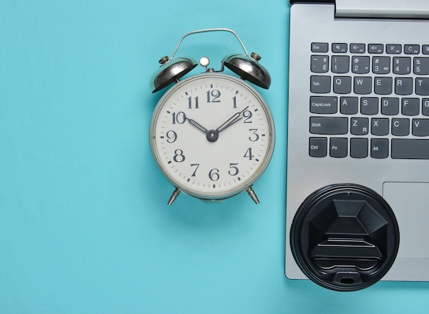 Laptop and coffee cup, alarm clock on blue paper