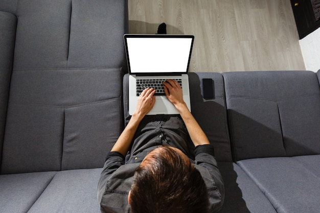 Laptop and coffee cup in girl's hands sitting on a wooden floor