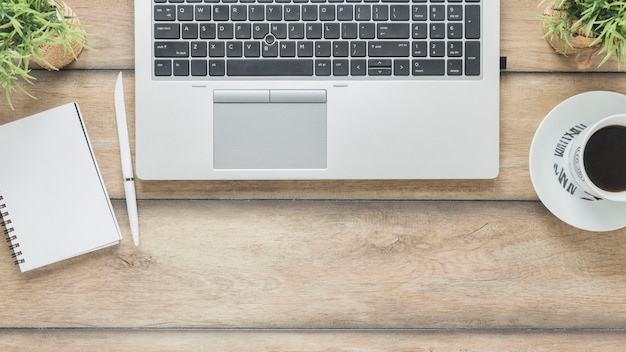 Laptop and coffee cup near notebook on table