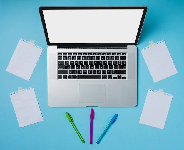 Laptop and colorful pens with papers stucked with tape on blue backdrop