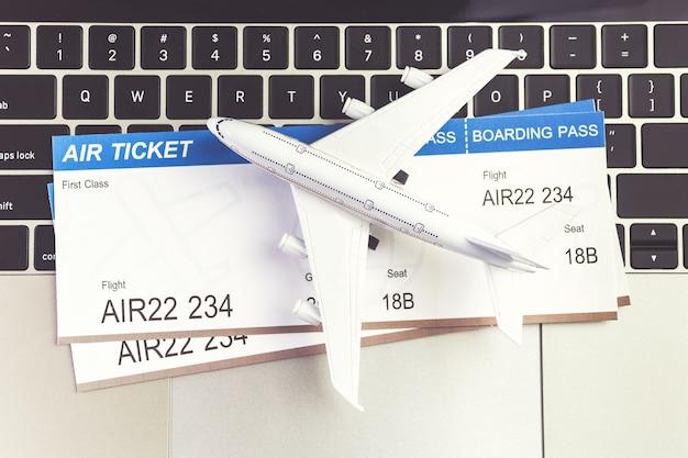 Портативный компьютер и самолет и деньги на столе. концепция онлайн-бронирования билетов