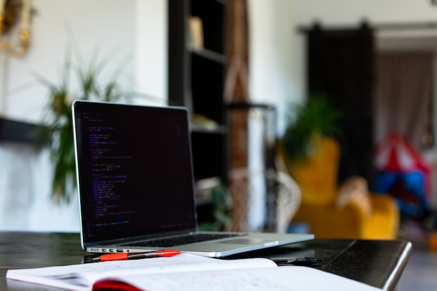 홈 오피스의 테이블에 펜이 있는 노트북 컴퓨터와 노트북