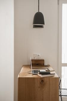 ラップトップコンピューターと木製のテーブル上のノートブック。