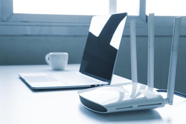 Портативный компьютер и роутер на столе