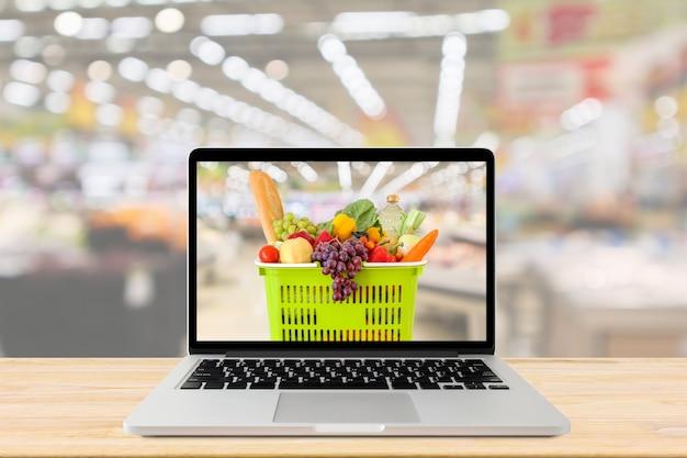 ラップトップコンピューターと木製のテーブルの食料品のオンラインコンセプトのショッピングバスケット