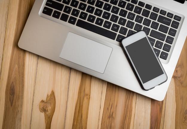 ラップトップコンピューターとスマートフォンの木製のテーブル
