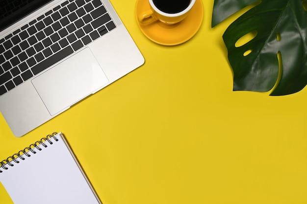 Портативный компьютер, чашка кофе и ноутбук на желтом фоне.