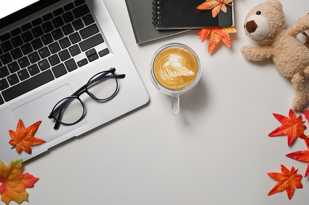Laptop computer, coffee cup, glasses, books and autumn maple leaves on white table.