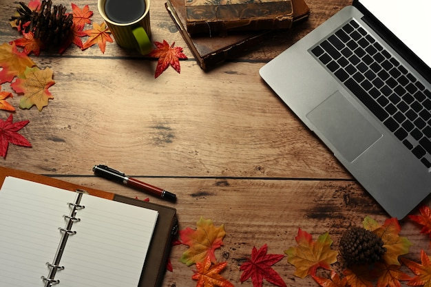 Laptop computer, coffee cup, notebook and autumn maple leaves on wooden table.