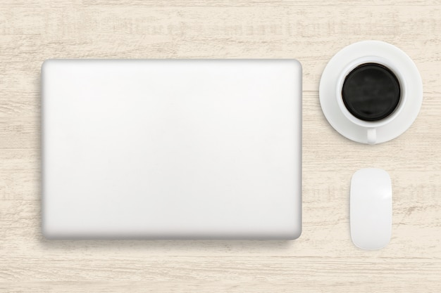 Laptop computer and a cup of coffee on wood table. top view business background.