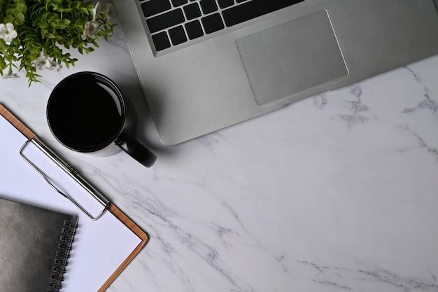 Портативный компьютер, чашка кофе, комнатное растение и буфер обмена на мраморном фоне.