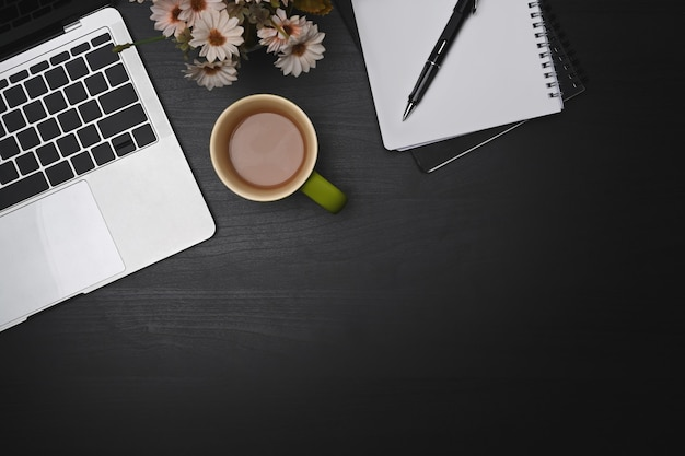 Портативный компьютер, пустой ноутбук и кофейная чашка на черном столе.