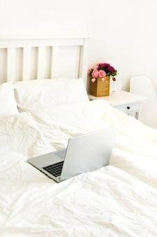 ベッドの上のラップトップコンピュータ。ホームオフィス、遠隔作業。ガジェット、ソーシャルネットワーク中毒