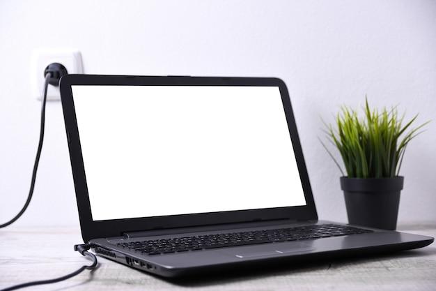 ラップトップ、コンピューターは壁の近くの机の220ボルトのコンセントから充電しています。エネルギー、蓄積。モックアップ