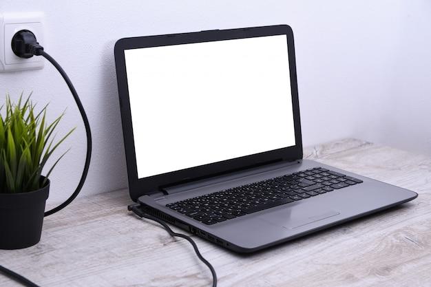 ラップトップ、コンピューターは、壁の近くの机にある220ボルトのコンセントから充電しています。エネルギー、蓄積。
