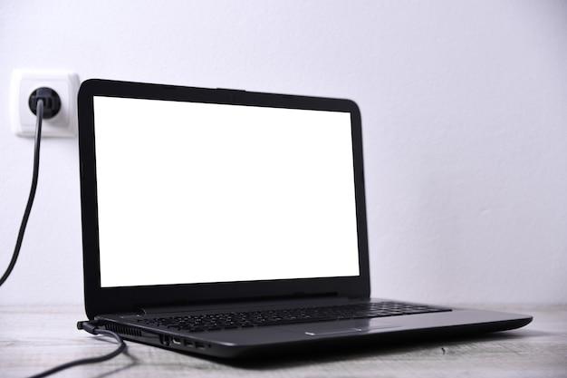 노트북, 컴퓨터는 벽 근처 책상에있는 220 볼트 콘센트에서 충전됩니다. 에너지, 축적.