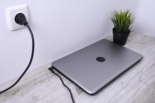 노트북, 컴퓨터는 벽 근처 책상에서 충전 중입니다. 에너지, 축적.