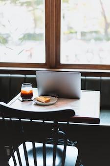 노트북 컴퓨터, 레몬 치즈 케이크 및 현대적인 레스토랑에서 커피 한 잔