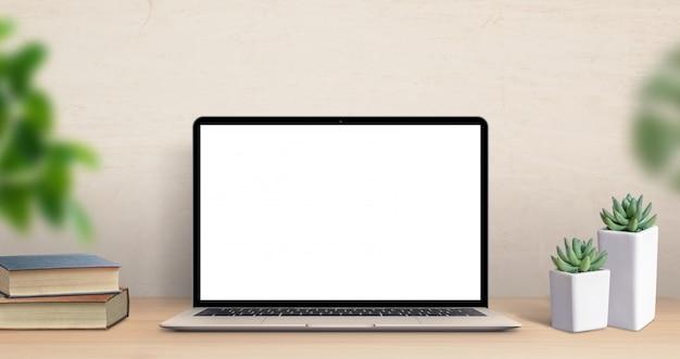 仕事机の上のラップトップコンピューターのモックアップ。植物とテーブルの上の本のクローズアップシーン。モダンで薄いノートパソコンのデザイン。モックアップ、アプリ、またはwebサイトのプロモーション用の分離された画面