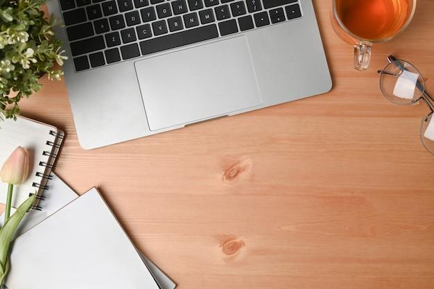 Портативный компьютер, ноутбук, чашка и очки на деревянном столе.