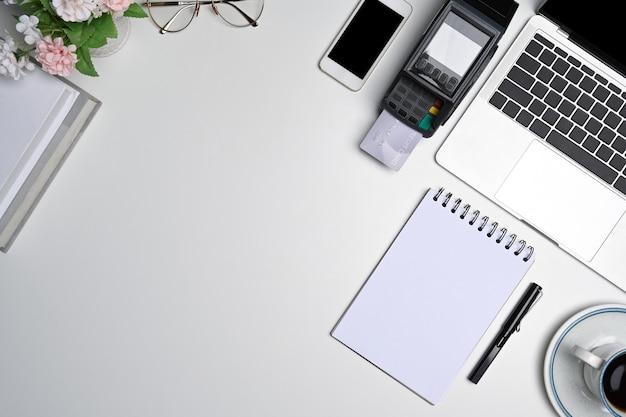 Портативный компьютер, ноутбук, мобильный телефон и платежный терминал на белом офисном столе.
