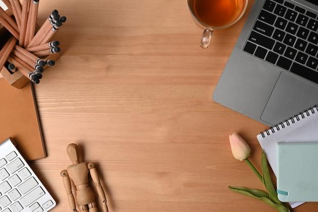 Портативный компьютер, блокнот, подставка для карандашей и чашка чая на деревянном столе.