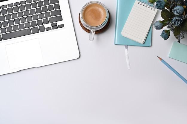 흰색 사무실 책상에 노트북 컴퓨터, 메모장, 커피 컵.