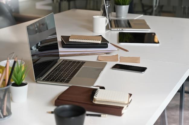 Портативный компьютер на столе переговоров в конференц-зале.