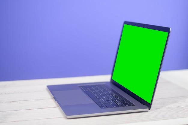 파란색 배경 위에 책상에 노트북 컴퓨터
