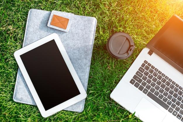 屋外公園のコーヒーカップとタブレットと緑の芝生の上のラップトップコンピューター。スペースをコピーします。静物。太陽フレア