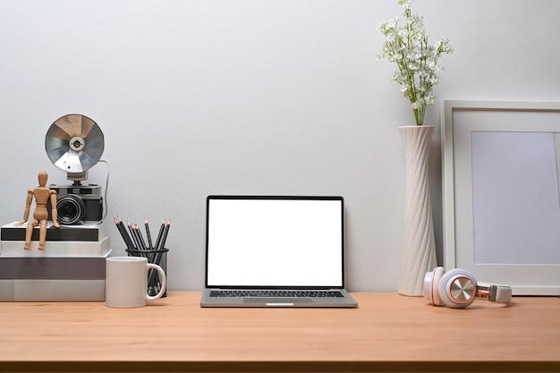 ラップトップコンピューター、フォトフレーム、本、鉛筆ホルダー、木製の机の上のヘッドフォン。